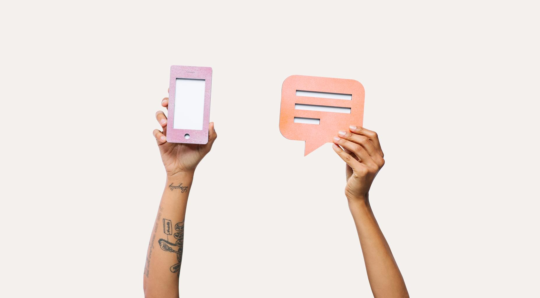 People holding up paper cut-outs of a cell phone and a messaging bubble